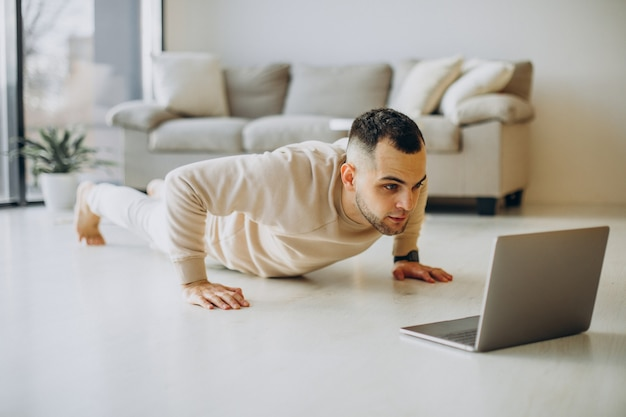 Giovane sportivo che pratica yoga a casa