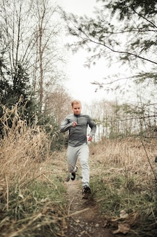Young sporty man running in forest