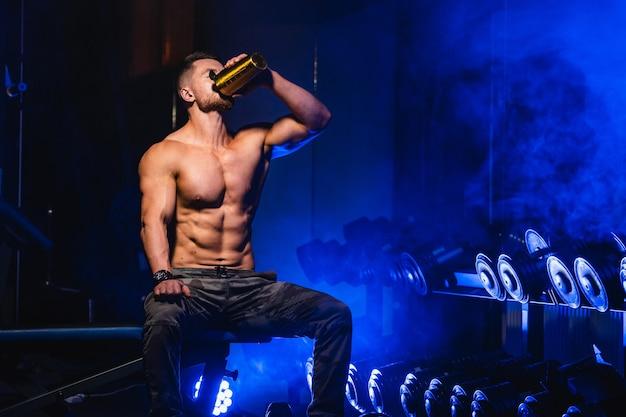 ランニングトラックに座って、ハードトレーニングの後に休んでいる若いスポーティな男。プロテインカクテルを飲む。上半身裸の筋肉質の体。閉じる。
