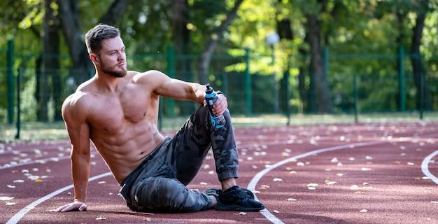 Молодой спортивный человек сидит на беговой дорожке и отдыхает после тяжелой тренировки на стадионе