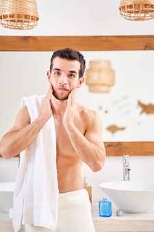 若いスポーティーな男は彼の首を洗い、バスルームの鏡の前で彼の肩にタオルで立っています