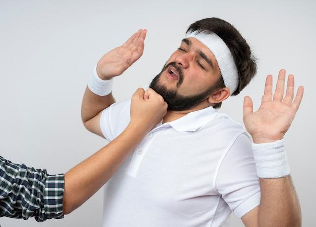 Молодой спортивный мужчина в повязке на голову и на запястье, избитый кем-то, поднимающим руки