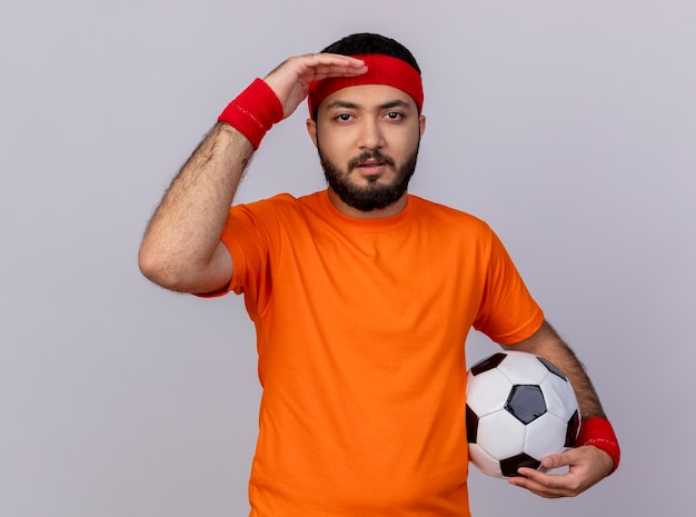Giovane uomo sportivo che indossa la fascia e il braccialetto che guarda l'obbiettivo con la mano che tiene la sfera isolata su priorità bassa bianca