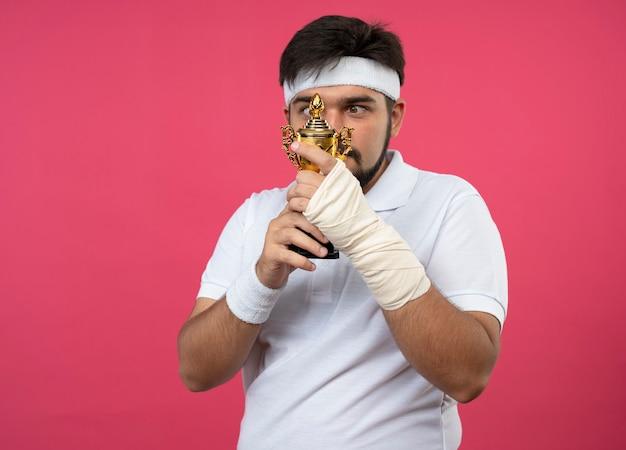Giovane uomo sportivo che indossa la fascia e il braccialetto con il polso avvolto con la benda che tiene e guardando la coppa del vincitore isolato sulla parete rosa con lo spazio della copia