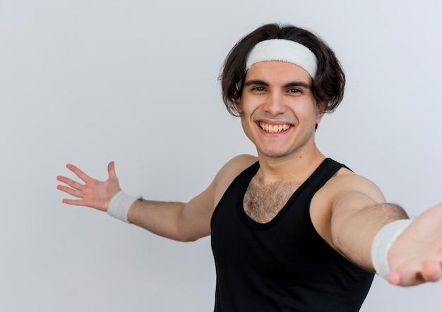 スポーツウェアとヘッドバンドを身に着けている若いスポーティな男は、白い壁の上に元気に立って幸せで前向きな笑顔で自分撮りをしています