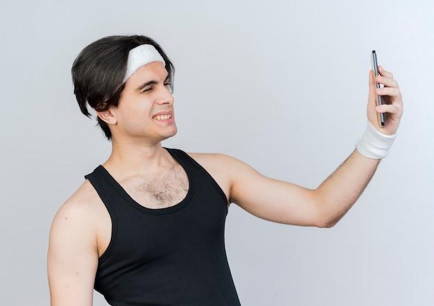 운동복을 입고 스포티 한 젊은이가 자신의 스마트 폰을 사용하여 셀카를하고 웃고 흰 벽 위에 서 윙크
