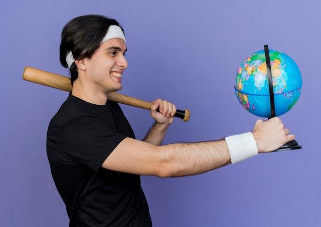 Молодой спортивный мужчина в спортивной одежде и повязке на голову, весело улыбаясь, держит бейсбольную биту и глобус