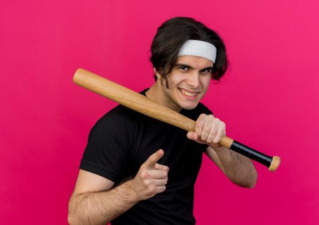 Молодой спортивный мужчина в спортивной одежде и повязке на голову держит пуантин с бейсбольной битой с указательным пальцем в камере, уверенно улыбаясь