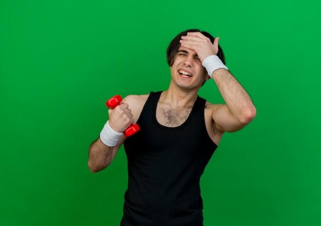彼の額に手と混同されているダンベルを保持しているスポーツウェアとヘッドバンドを身に着けている若いスポーティな男