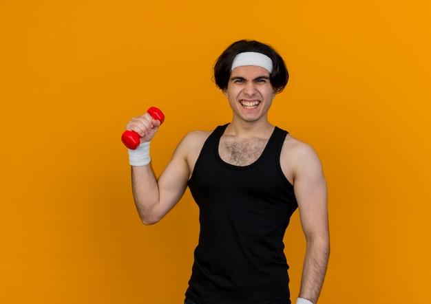 Молодой спортивный мужчина в спортивной одежде и повязке на голову, держащий гантели, делает упражнения, выглядя напряженными, стоя над оранжевой стеной