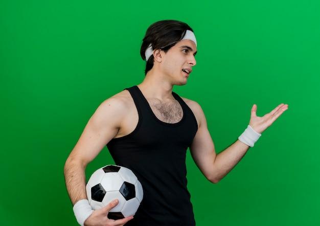 스포츠웨어와 머리띠를 착용하고 축구 공을 들고 스포티 한 젊은이가 요청처럼 팔을 옆으로 바라보고 있습니다.