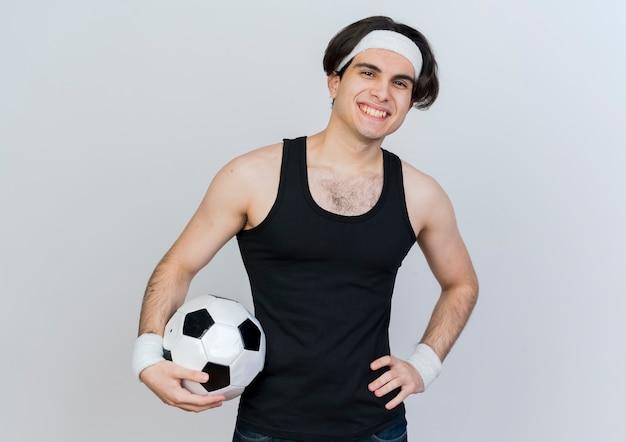 Молодой спортивный мужчина в спортивной одежде и повязке на голову с футбольным мячом, глядя вперед, улыбаясь, со счастливым лицом, стоящим над белой стеной