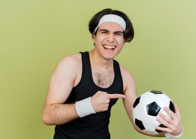 행복 한 얼굴로 웃 고 그것에 검지 손가락으로 가리키는 축구 공을 들고 운동복과 머리띠를 착용하는 젊은 스포티 한 남자