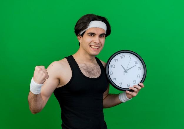 Молодой спортивный мужчина в спортивной одежде и повязке на голову держит настенные часы, сжимая кулак, счастлив и взволнован