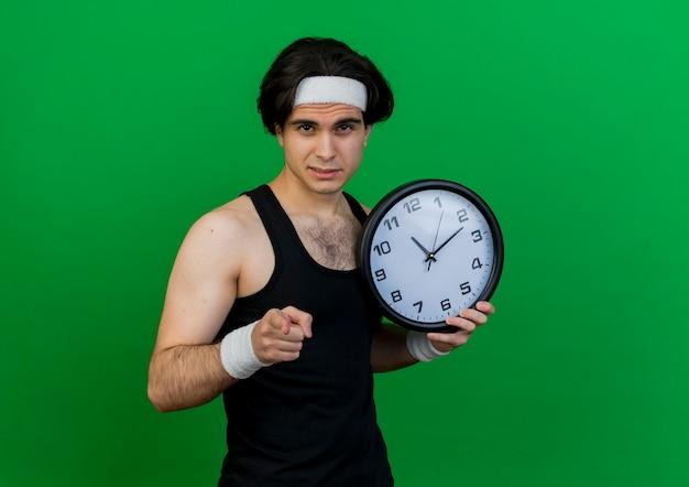 Молодой спортивный мужчина в спортивной одежде и повязке на голову держит настенные часы, указывая указательным пальцем на камеру с серьезным лицом