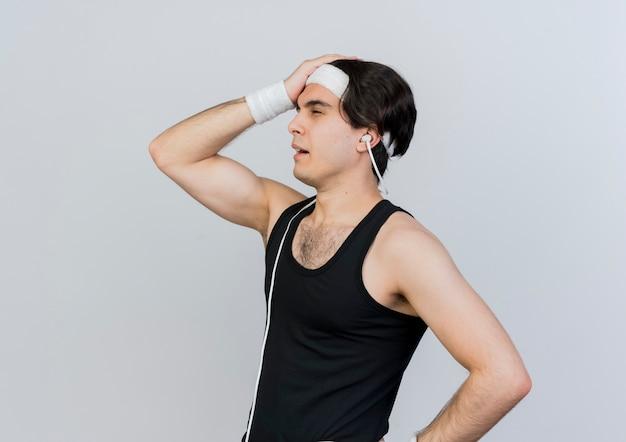 白い壁の上に立って混乱している彼の頭に手を置いて脇を見てスポーツウェアとヘッドバンドを身に着けている若いスポーティな男