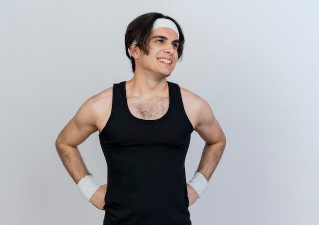 白い壁の上に立っている顔に笑顔で脇を見てスポーツウェアとヘッドバンドを身に着けている若いスポーティな男