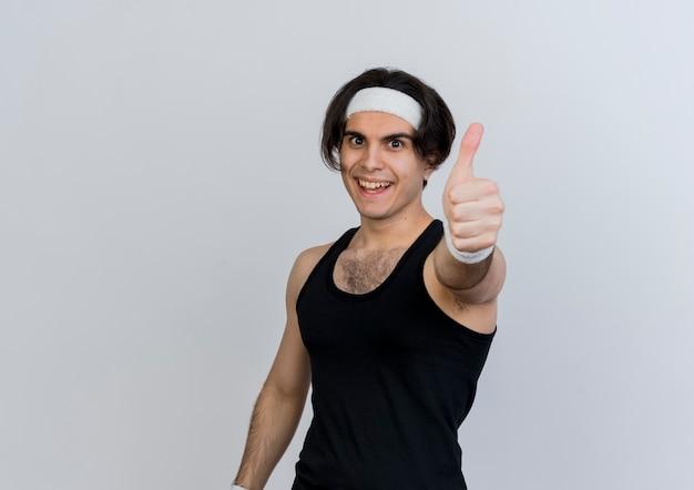 흰색 벽 위에 서 엄지 손가락을 보여주는 웃 고 앞을보고 운동복과 머리띠를 착용하는 젊은 스포티 한 남자