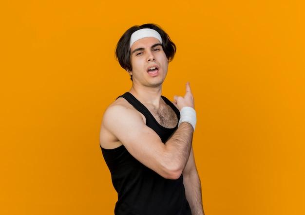 오렌지 벽 위에 다시 서 가리키는 자신감 식으로 앞을보고 운동복과 머리띠를 착용하는 스포티 한 젊은이