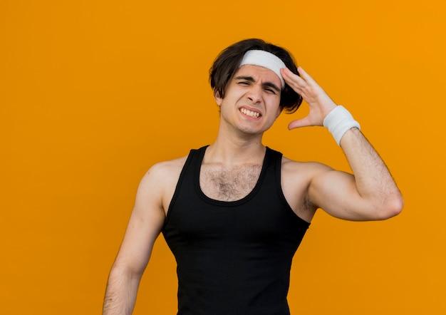 スポーツウェアとヘッドバンドを身に着けている若いスポーティな男は、間違いのために彼の頭の上の手と混同しているように見えます