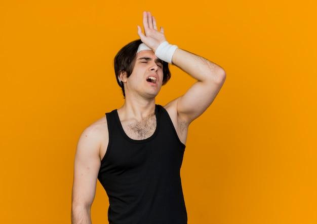 오렌지 벽 위에 서있는 운동 후 피곤하고 지친 찾고 운동복과 머리띠를 착용하는 스포티 한 젊은이