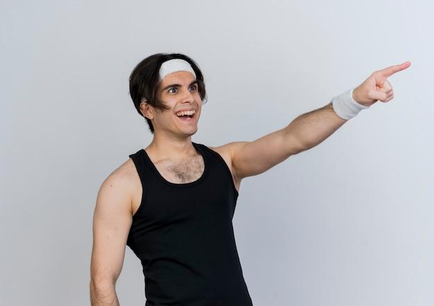 Молодой спортивный мужчина в спортивной одежде и повязке на голову, указывая указательным пальцем на что-то весело улыбаясь, стоя над белой стеной