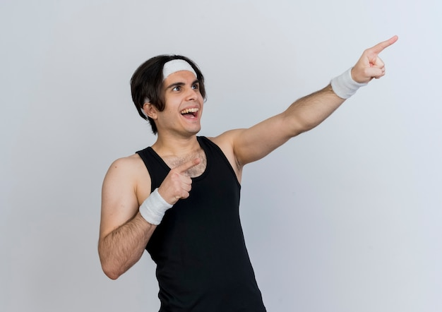 Молодой спортивный мужчина в спортивной одежде и повязке на голову, указывая указательными пальцами на что-то весело улыбаясь, стоя над белой стеной