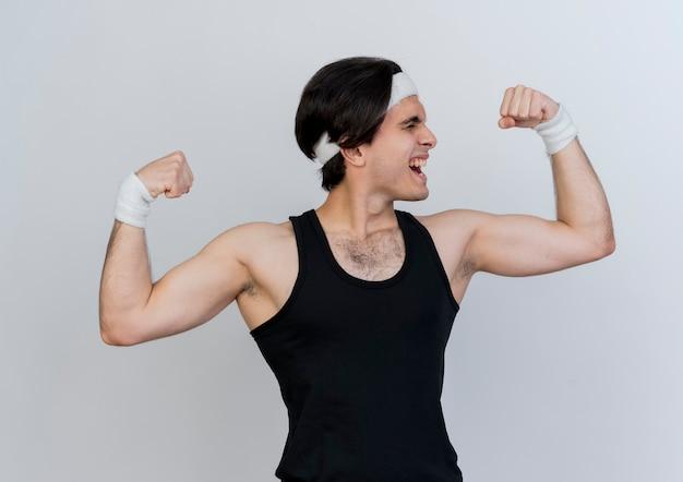 운동복을 입고 스포티 한 젊은이가 힘과 팔뚝을 보여주는 주먹을 높이고 흰 벽 위에 서있는 긴장된 모습을보고 있습니다.