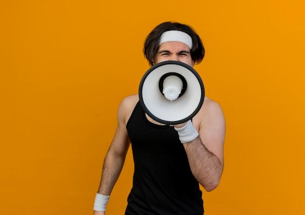 오렌지 벽 위에 서있는 확성기에 외치는 운동복과 머리띠를 착용하는 스포티 한 젊은이