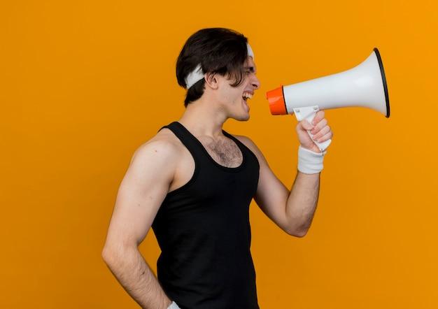 Молодой спортивный мужчина в спортивной одежде и повязке на голову кричит в мегафон
