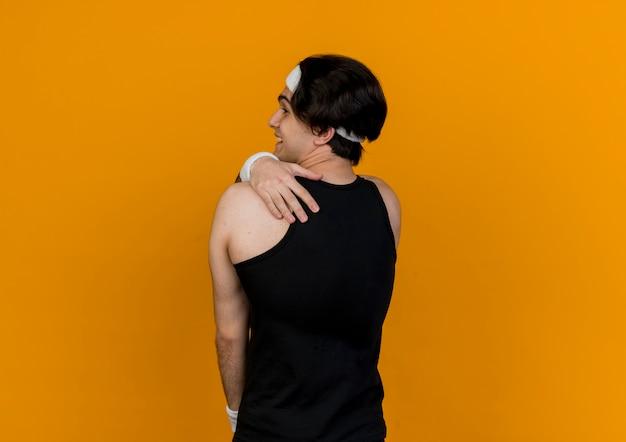 Молодой спортивный мужчина в спортивной одежде и повязке на голову стоит спиной, касаясь его плеча через оранжевую стену
