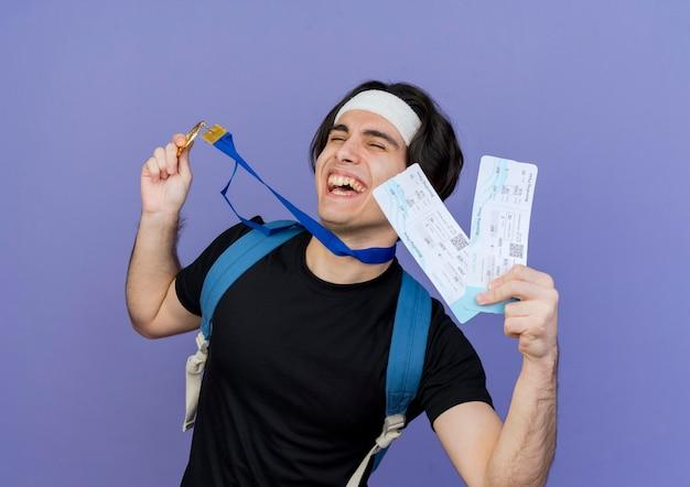 スポーツウェアとヘッドバンドを身に着けている若いスポーティな男は、バックパックと首の周りに金メダルを持って航空券を持っていますクレイジー幸せな笑い