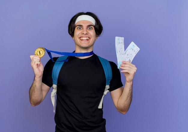 スポーツウェアとヘッドバンドを身に着けている若いスポーティな男は、バックパックと首の周りに金メダルを持って航空券を持ってカメラを見て笑ってクレイジーハッピー