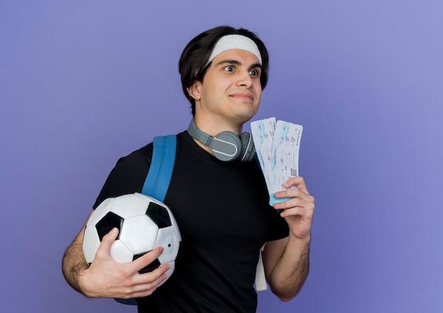 축구 공과 항공 티켓을 들고 배낭을 들고 운동복과 머리띠를 착용하는 스포티 한 젊은이
