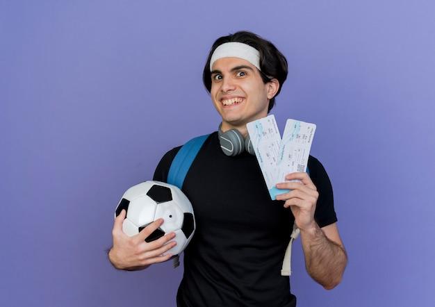 행복 한 얼굴로 웃 고 축구 공과 항공 티켓을 들고 배낭 운동복과 머리띠를 착용하는 젊은 스포티 한 남자