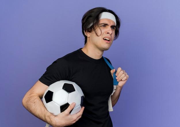 축구 공을 들고 배낭과 함께 운동복과 머리띠를 착용하는 젊은 스포티 한 남자가 혼란스럽고 불쾌 해합니다.