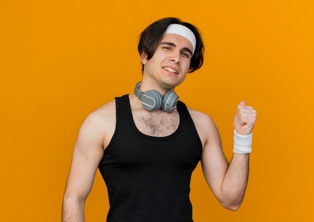 오렌지 벽 위에 다시 서있는 웃는 전면을보고 목 주위에 헤드폰으로 운동복과 머리띠를 착용하는 젊은 스포티 한 남자