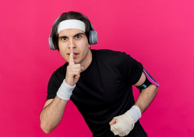 Молодой спортивный мужчина в спортивной одежде и повязке на голову с наушниками и повязкой для смартфона делает жест тишины с пальцем на губах
