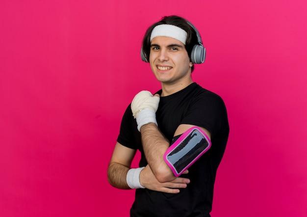 スポーツウェアとヘッドバンドを身に着けている若いスポーティな男は、自信を持って幸せで前向きな笑顔のヘッドフォンとスマートフォンのアームバンド
