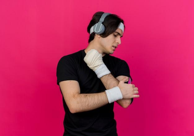Молодой спортивный мужчина в спортивной одежде и повязке на голову с наушниками и повязкой для смартфона, касаясь его серьезным лицом