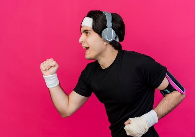 Молодой спортивный мужчина в спортивной одежде и повязке на голову с наушниками и повязкой для смартфона усердно тренируется