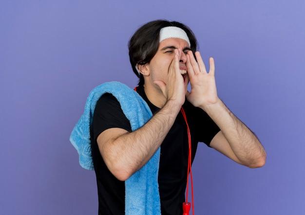 어깨 전화에 목과 수건 주위에 밧줄을 건너 뛰거나 입 근처에 손으로 외치는 운동복과 머리띠를 착용하는 젊은 스포티 한 남자