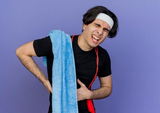 スポーツウェアとヘッドバンドを身に着けている若いスポーティな男性は、首に縄跳びをし、肩にタオルをかけ、腹痛に苦しんでいるように見えます。