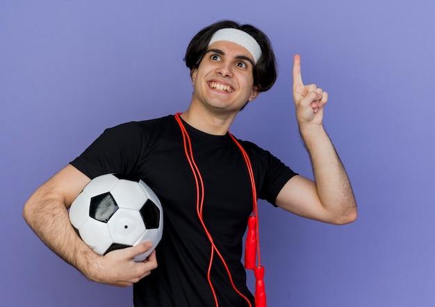 새로운 아이디어를 갖는 미소 손가락으로 축구 공 pointign를 들고 목 주위에 밧줄을 건너 뛰는 운동복과 머리띠를 착용하는 젊은 스포티 한 남자