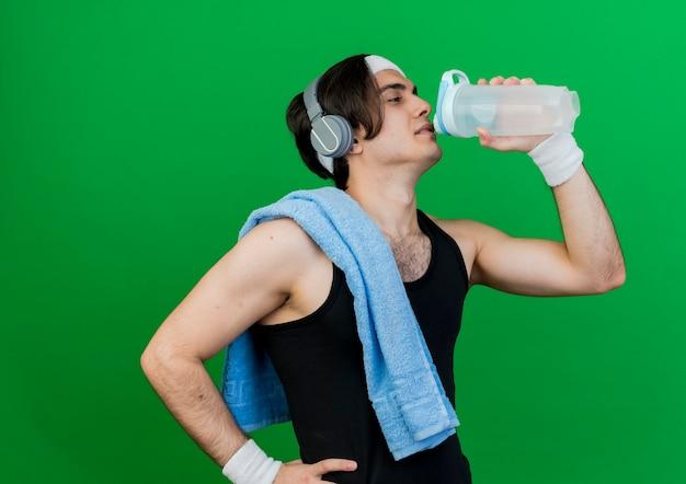 Молодой спортивный мужчина в спортивной одежде и повязке на голову с полотенцем на плече, пьющим воду после тренировки
