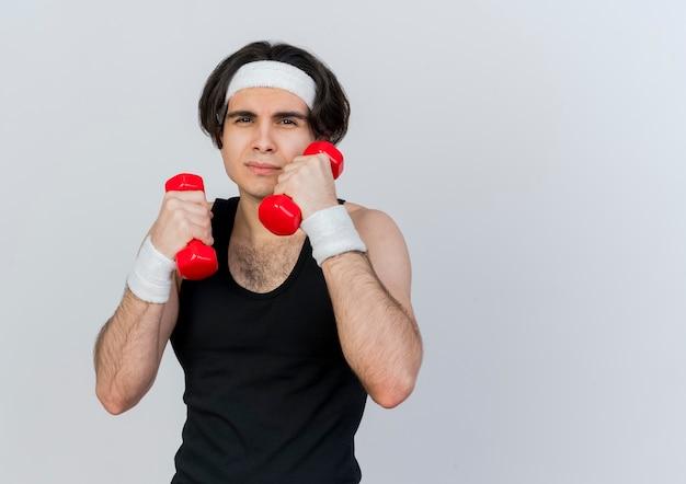 운동복과 머리띠를 착용하는 젊은 스포티 한 남자가 흰 벽 위에 서있는 심각한 얼굴로 정면을보고 아령으로 운동