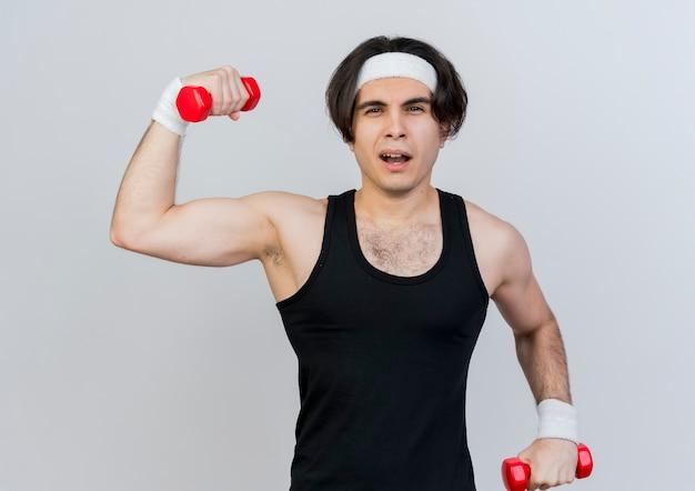 운동복과 머리띠를 착용하는 젊은 스포티 한 남자가 흰 벽 위에 자신감이 서있는 아령으로 운동을합니다.