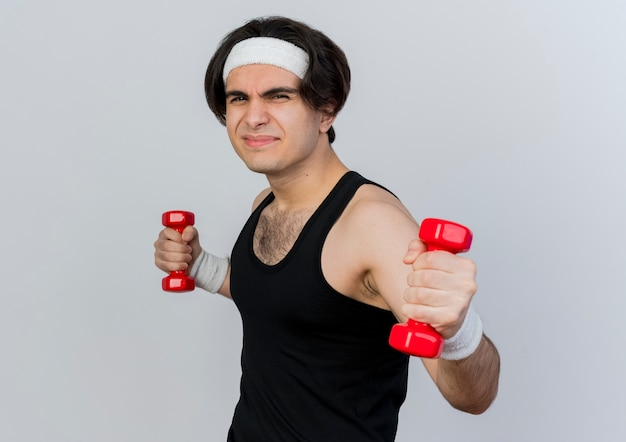 운동복과 머리띠를 착용하고 아령으로 운동하는 스포티 한 젊은이가 흰 벽 위에 서서 불쾌감을 느끼게합니다.