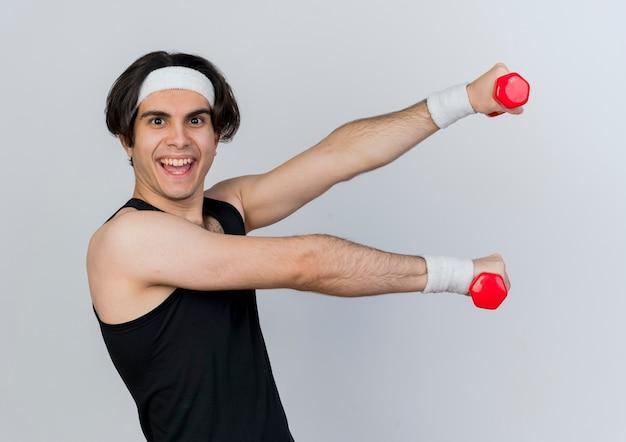 운동복과 머리띠를 착용하는 젊은 스포티 한 남자가 흰 벽 위에 서있는 행복한 얼굴로 웃는 아령으로 운동
