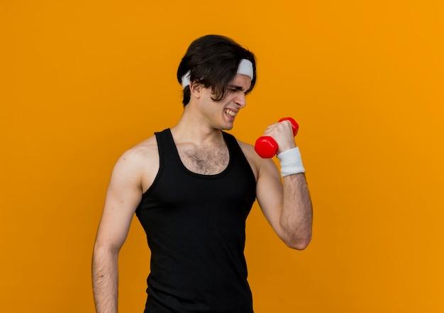 Giovane uomo sportivo che indossa abbigliamento sportivo e fascia tenendo il manubrio facendo esercizi cercando tesa